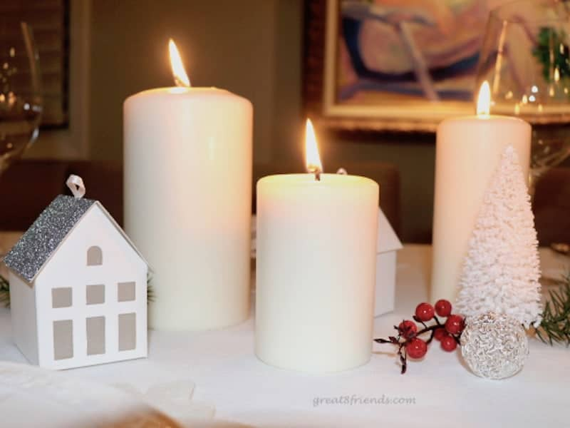 A close of Christmas centerpiece with lit candles and small paper house.