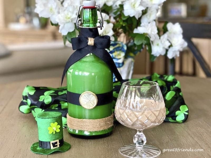 Irish Cream in a green bottle decorated for St. Patrick's Day. With a crystal snifter filled with Irish Cream.