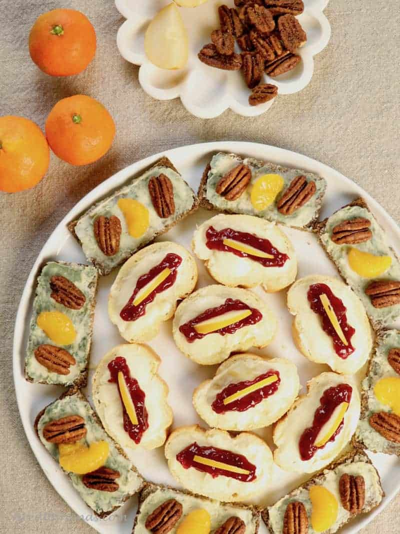 A round tray of cheese and fruit open faced sandwiches.