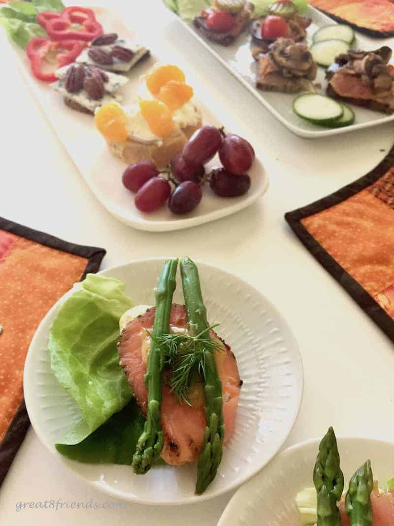 A table set with smorrebrod, with a small plate of a salmon and asparagus sandwich.