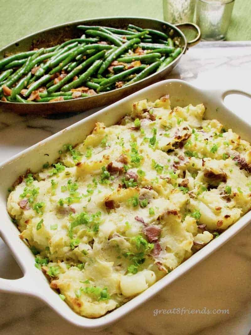 Cheesy Smashed Potato Casserole with green beans behind.