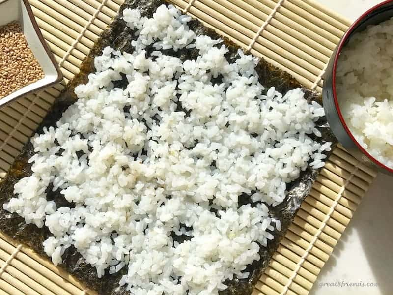 A sheet of seaweed covered with rice ready to add fish and veggies.