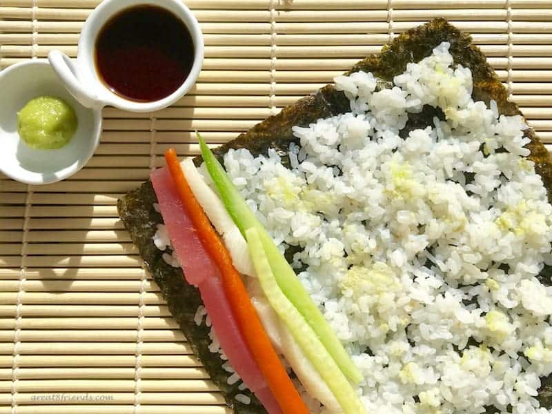 A sheet of seaweed covered with rice with veggies and fish ready to be rolled.