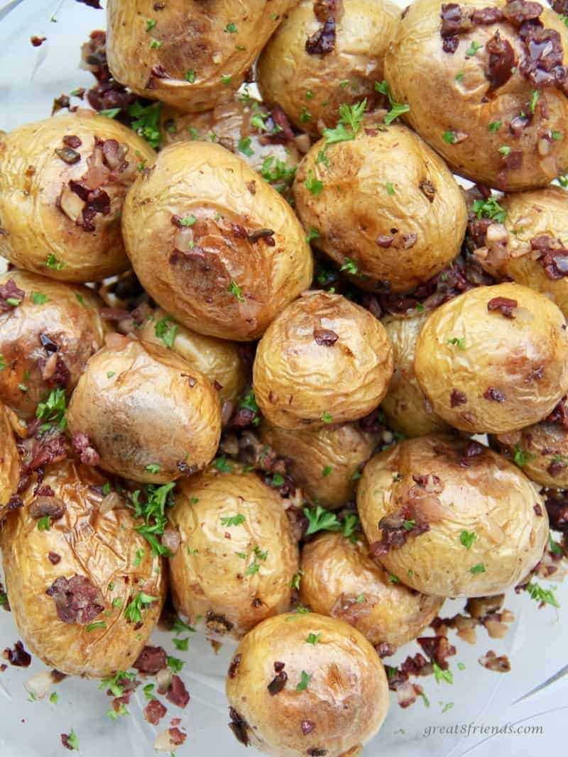Upclose photo of dirty potatoes which are potatoes with an olive tapenade.