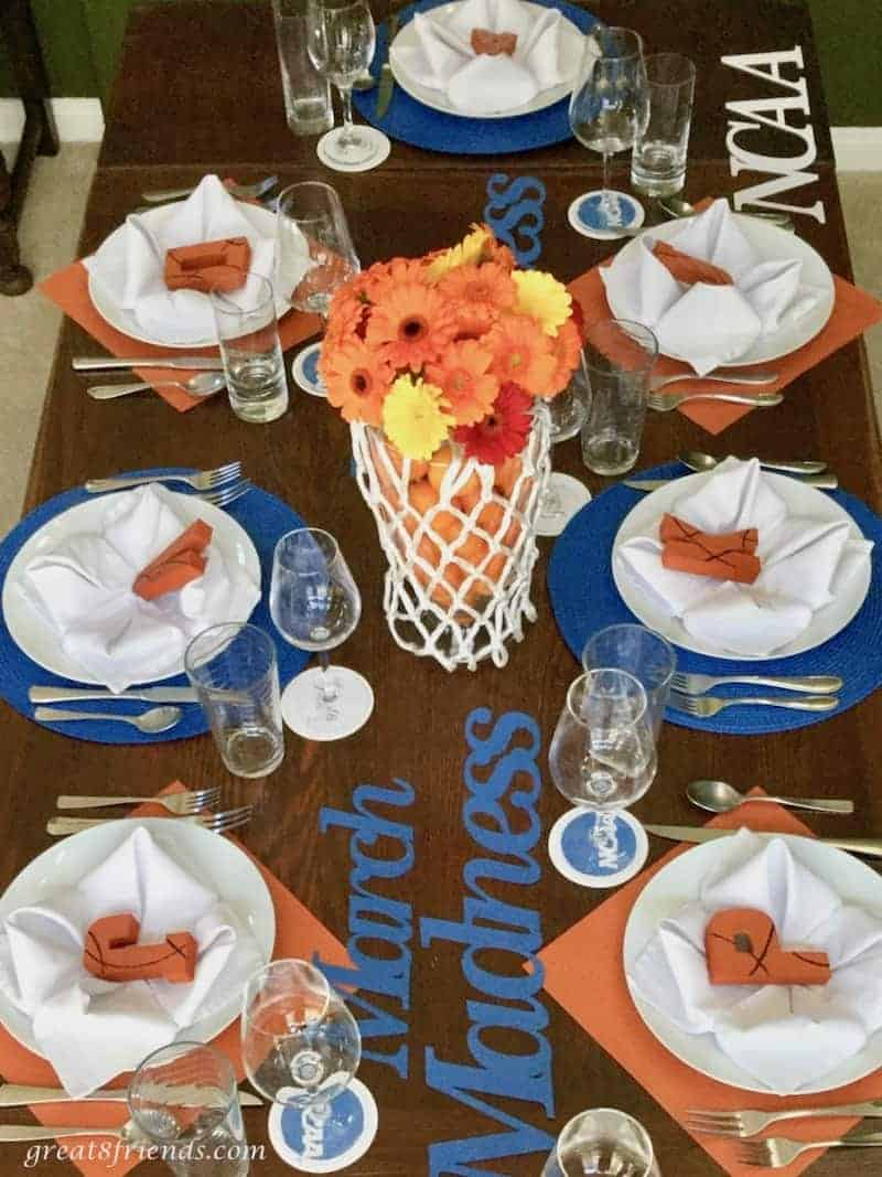 Overhead shot of our March Madness dinner table with a basketball hoop filled with orange and yellow gerbers as the centerpiece.