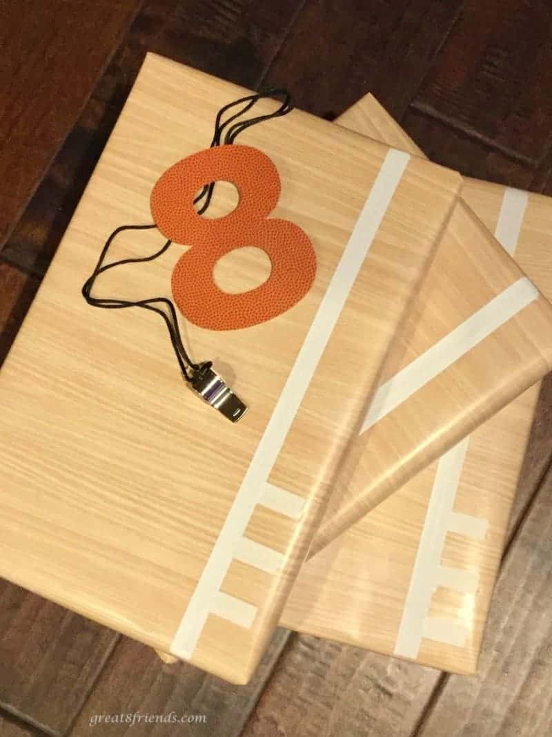 Three gifts wrapped in wood looking paper with masking tape lines (to look like a basketball court) with a cut out 8 and a whistle.