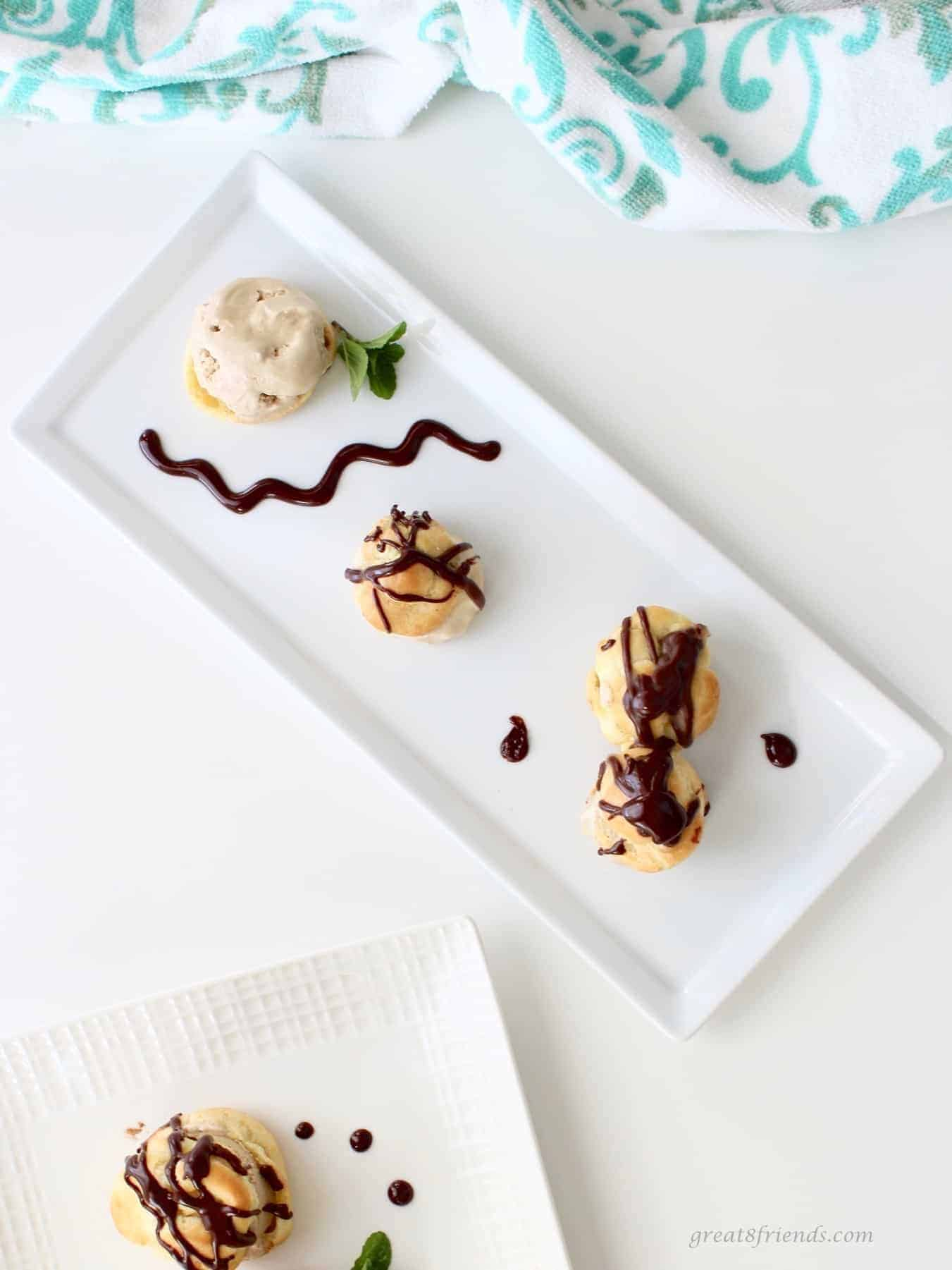 Profiteroles with coffee ice cream and chocolate sauce on a white rectangular plate.