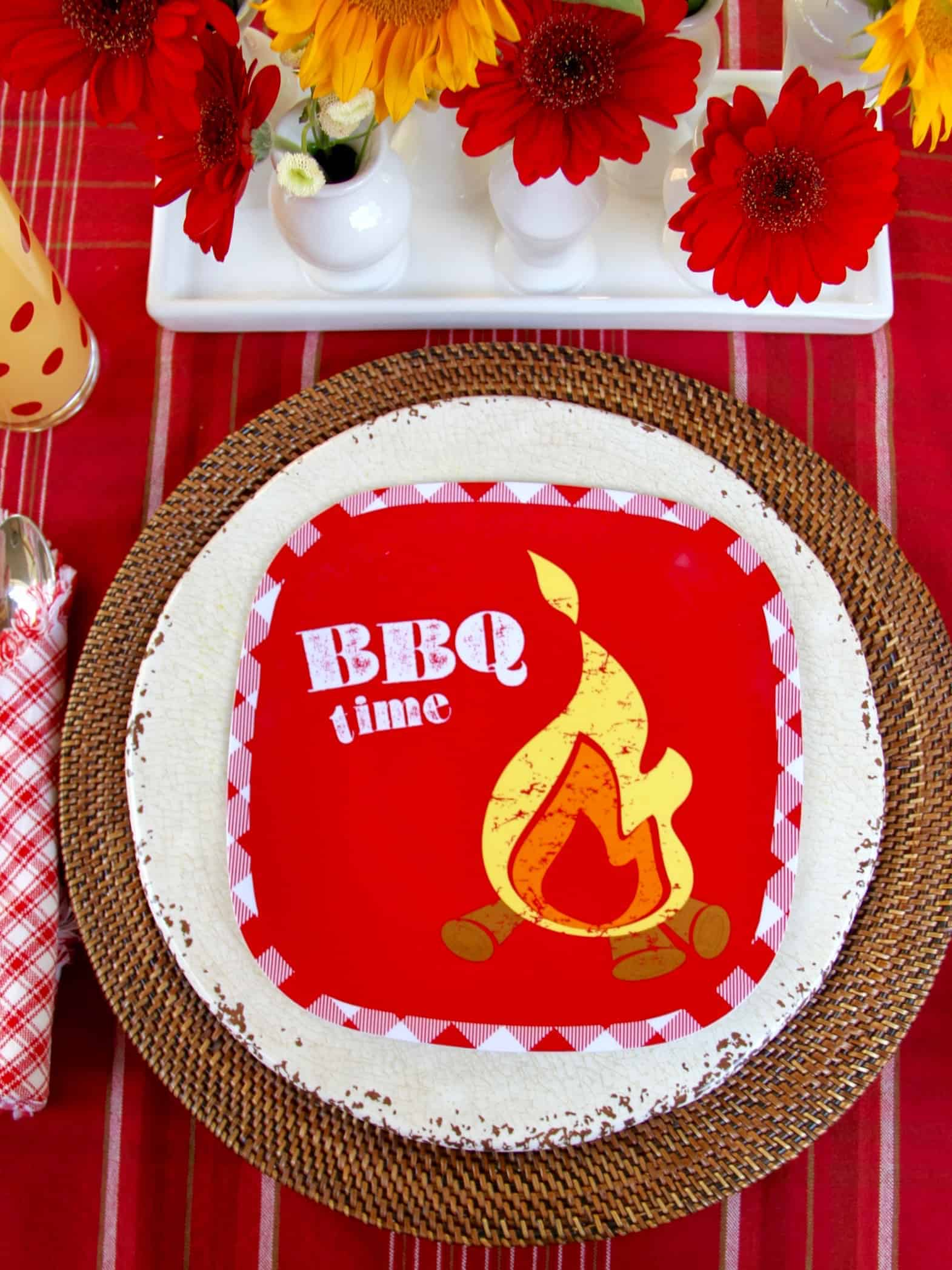 A place setting at a backyard barbecue using a bright red plate that says BBQ time on it.