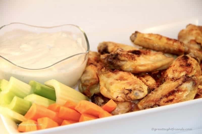 Chicken wings, carrot and celery sticks with a white dip in a white oblong serving dish.