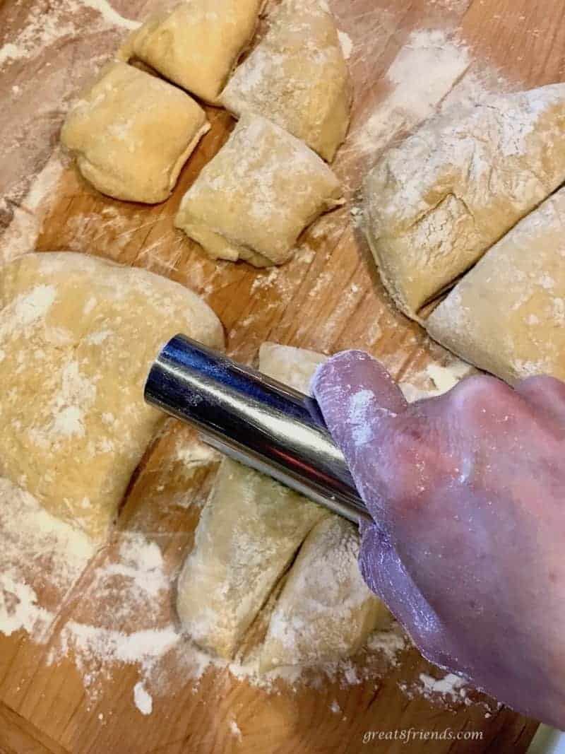 Hawaiian Bread dough being cut with a dough scraper into smaller rolls on a wood board covered with flour.