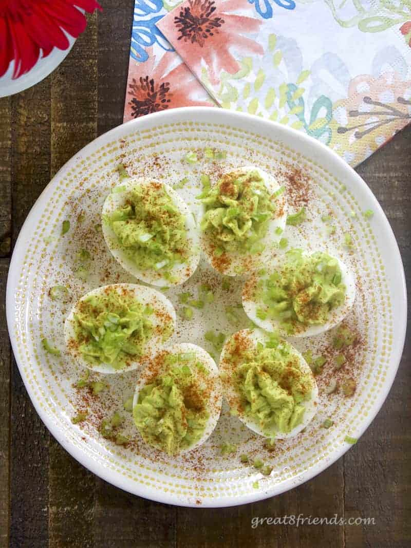 Overhead view of avocado deviled eggs on a white plate.