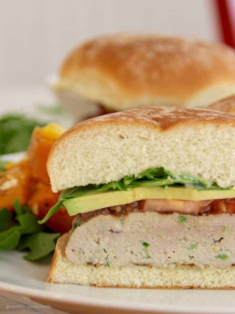 Unclose view of cut in half tuna burger with tomato, avocado, and arugula on a bun.