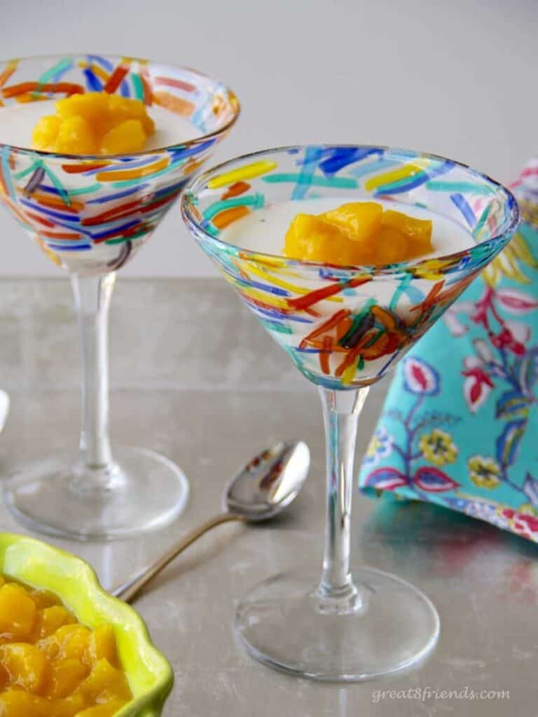 Two martini glasses filled with vanilla panna cotta and topped with mango compote.