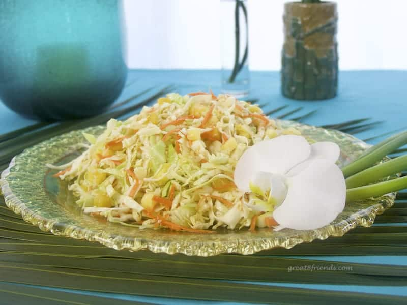 A round platter of Pineapple Sesame Slaw garnished with an orchid sitting on a palm leaf.