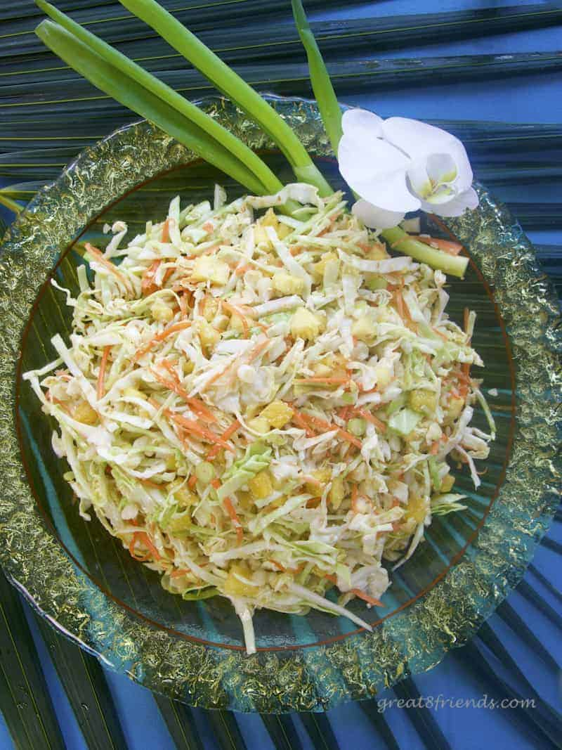 Overhead shot of Pineapple Sesame Slaw in a yellow glass bowl garnished with spring onions and an orchid.