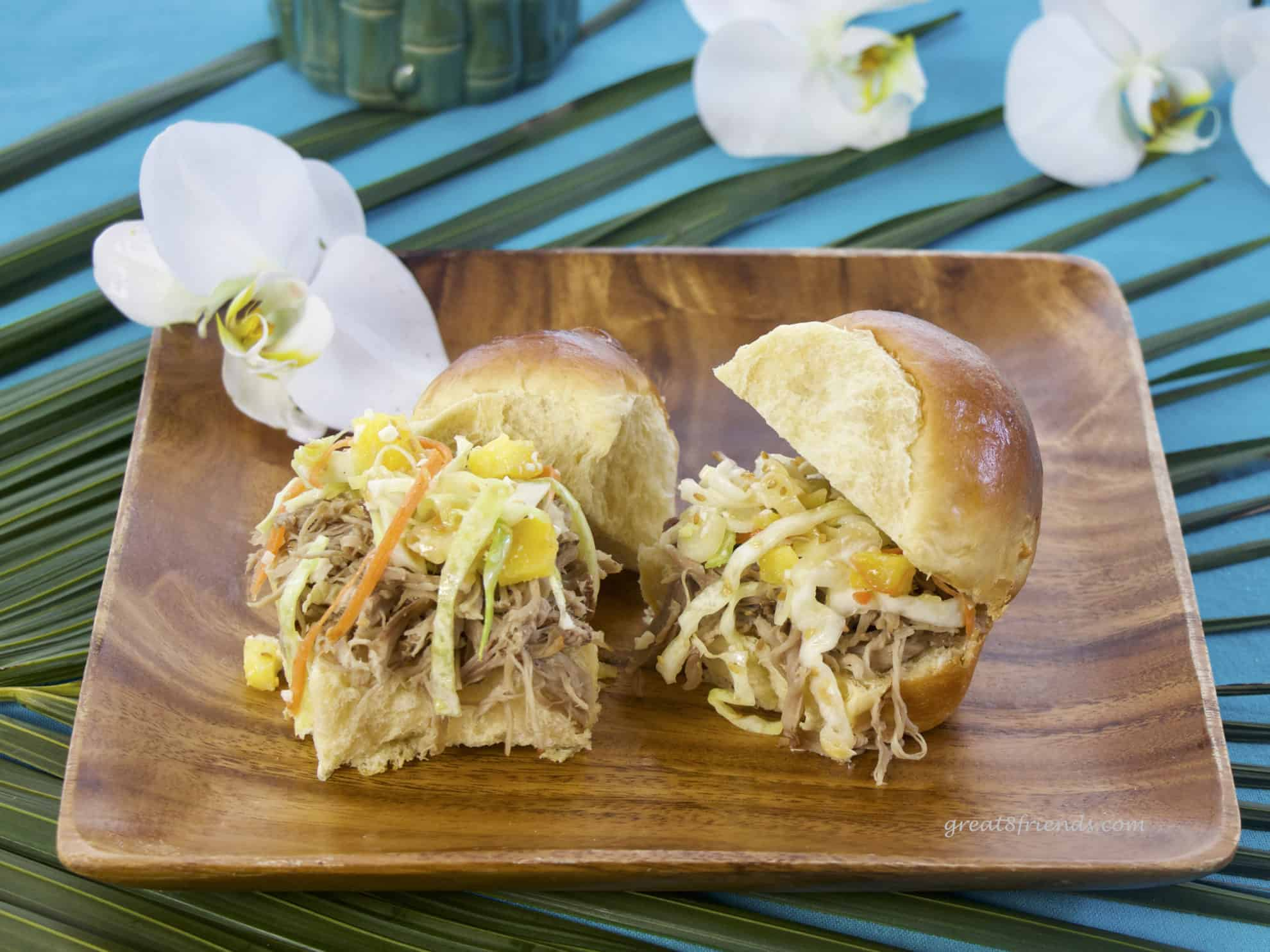 Two pulled pork sandwiches on Hawaiian sweet rolls sitting on a square wooden plate garnished with an orchid.