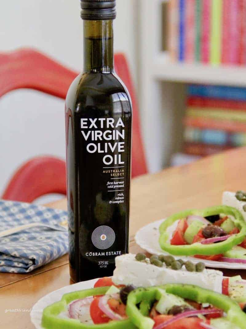Two plated greek salads and a bottle of Cobram Estate Olive Oil.