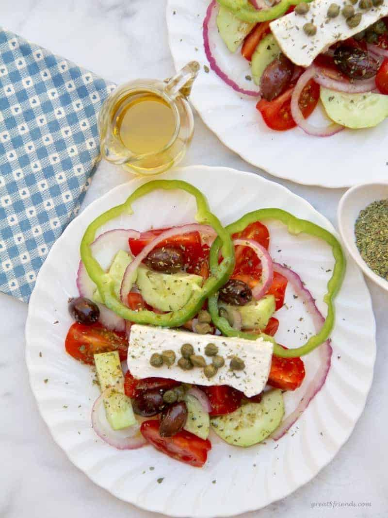 Overhead view of two Greek Salad plates with small pitcher of olive oil  and oregano on the side.