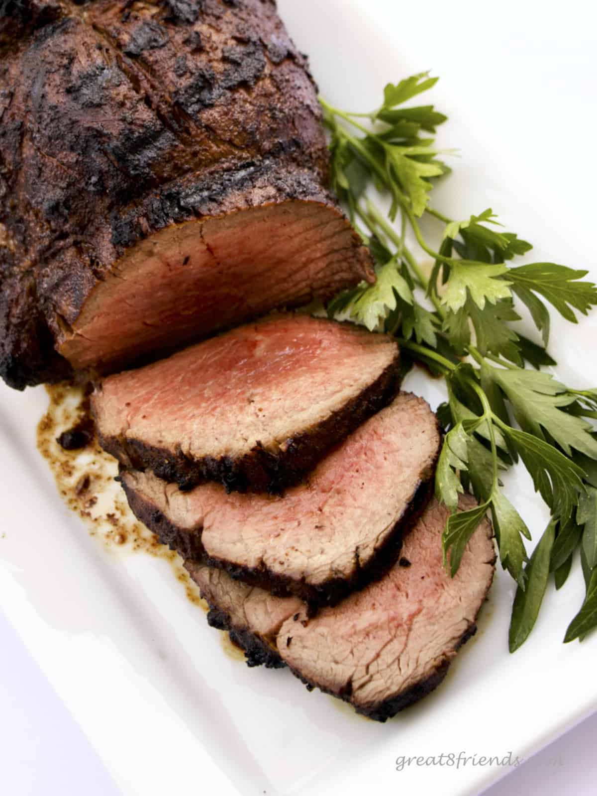A Grilled Beef Tenderloin with 3 slices fanned out surrounded by parsley.