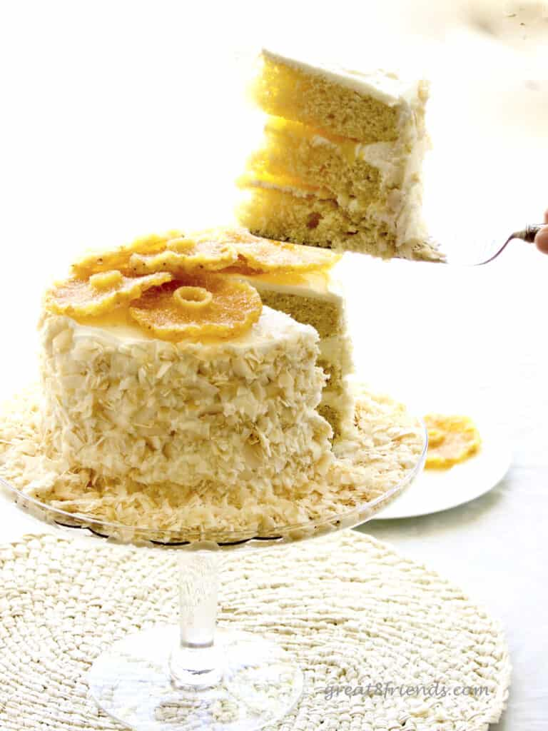 Slice of cake being lifted out of the whole cake. Cake has toasted coconut on the sides and candied pineapple on top.