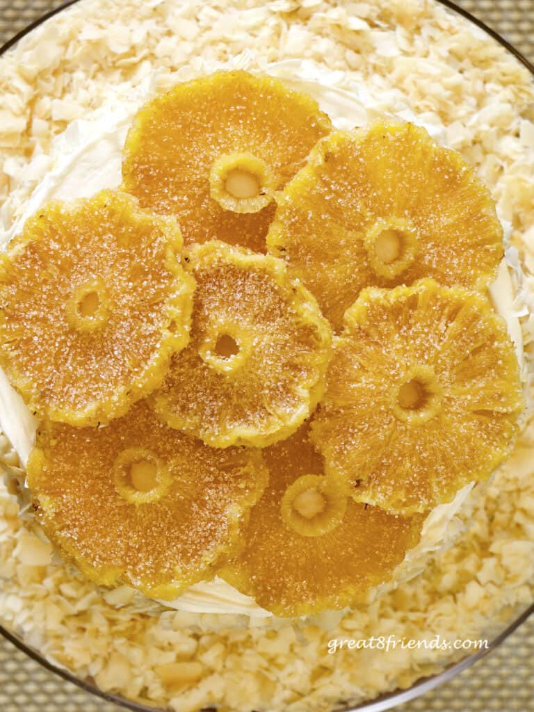 Overhead shot of round slices of candied pineapple laid on a cake.
