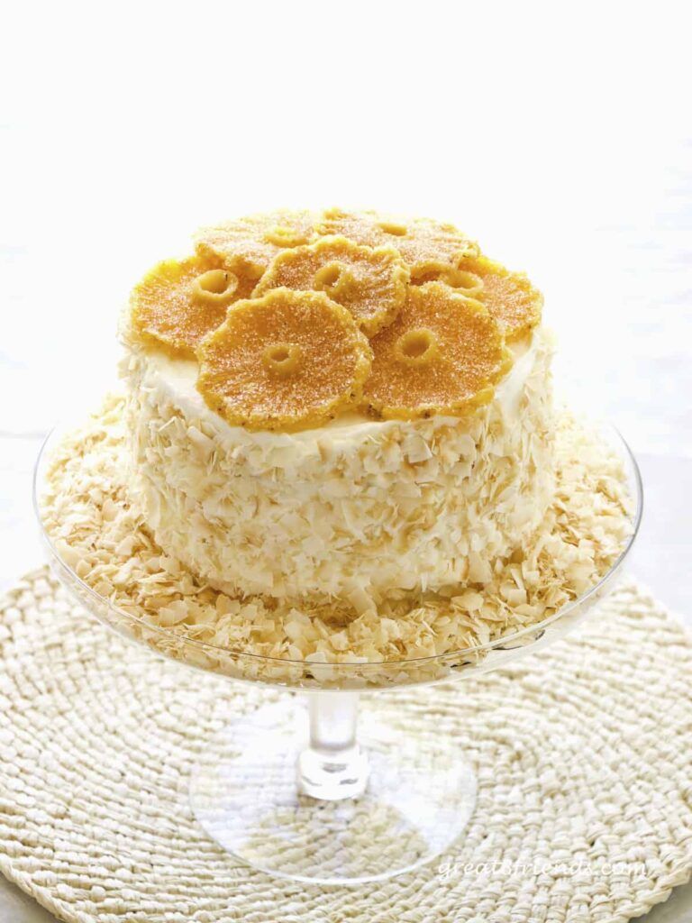 Pineapple Rum Cake with sides covered with toasted coconut and topped with round slices of candied pineapple. The cake in on a glass pedestal.