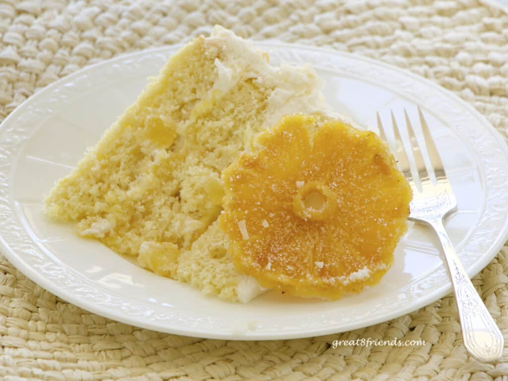 A slice of yellow cake laying on a white plate with a piece of candied pineapple propped against it.
