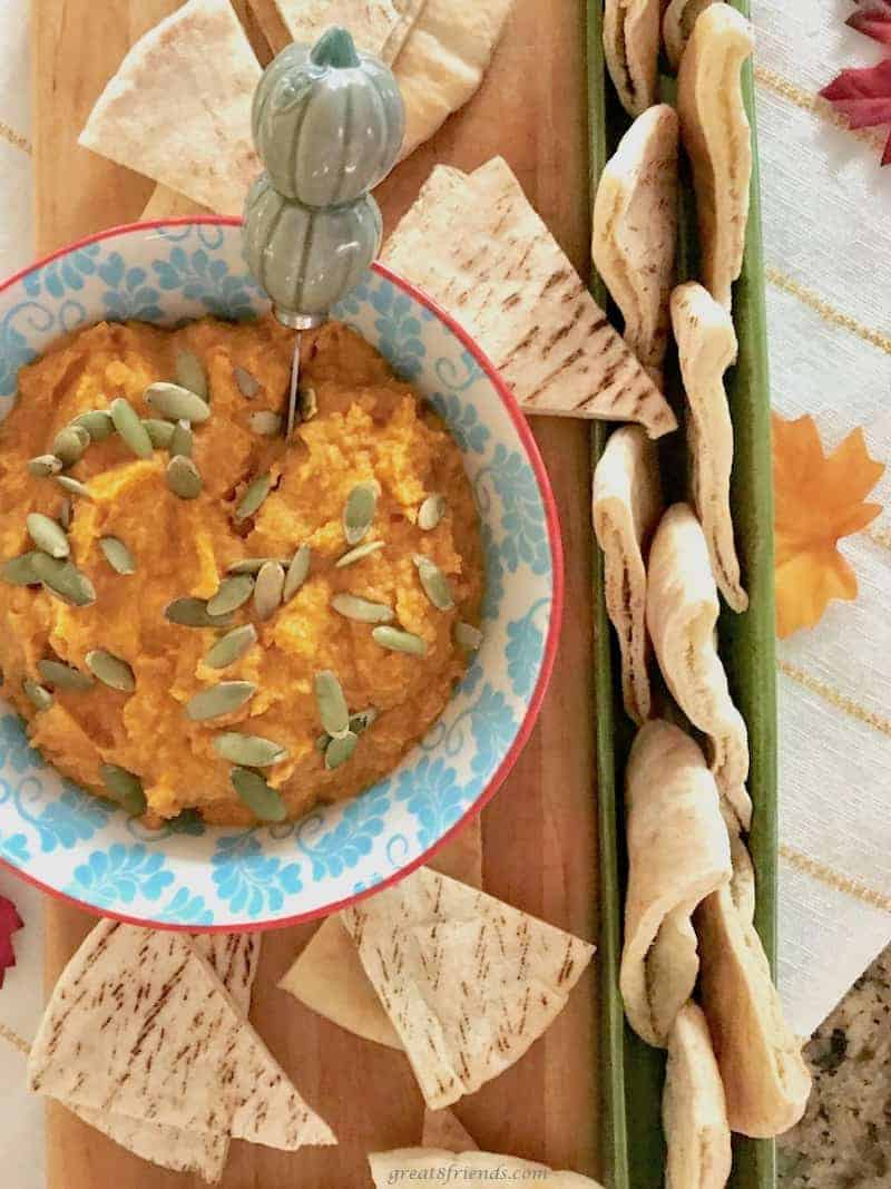 White bean pumpkin hummus served with pita bread pieces.