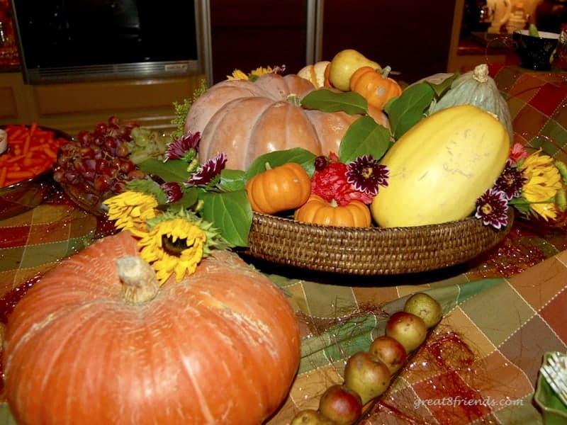 A centerpiece of pumpkins, gourds and flowers.