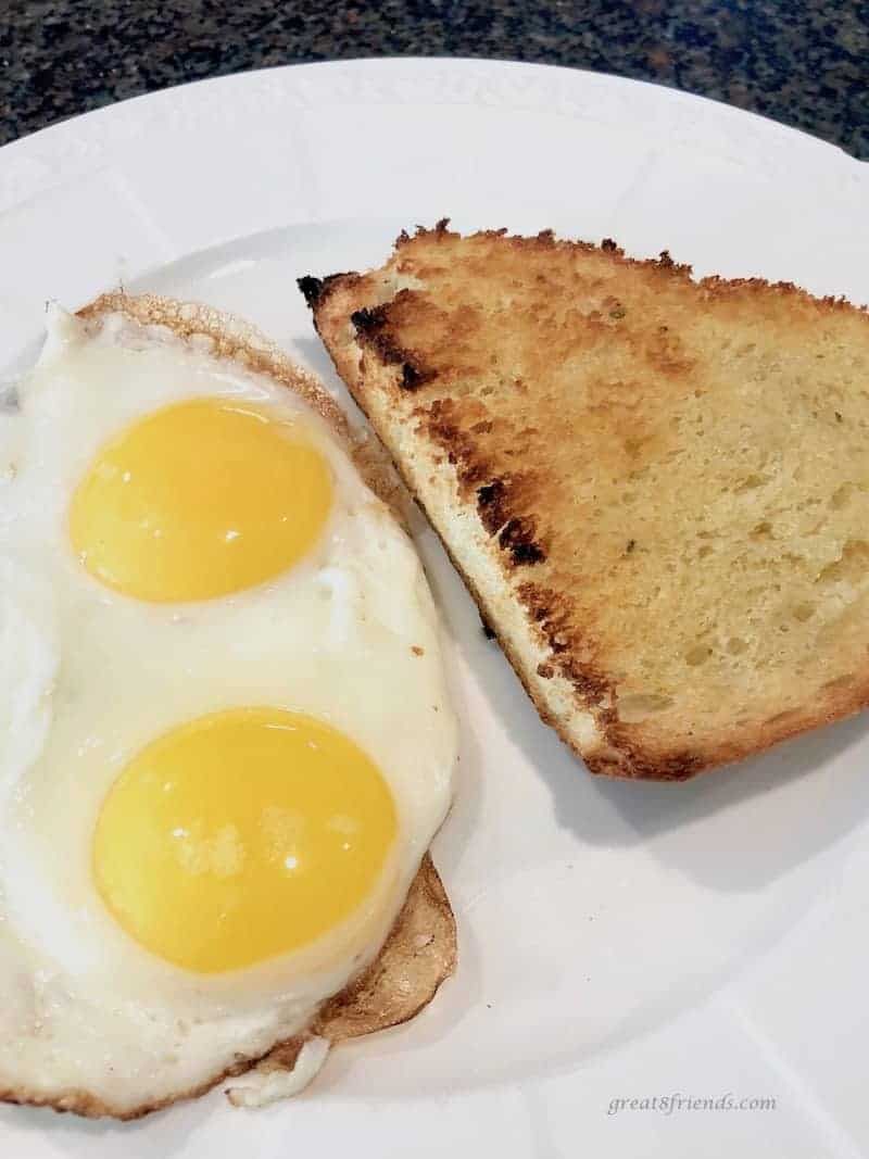 Toasted Onion Thyme Focaccia Bread with two fried eggs served on a white plate.