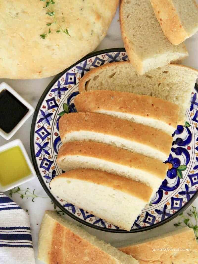 Sliced Savory Onion Thyme Focaccia Bread served on a blue colorful plate with olive oil and balsamic vinegar on the side.
