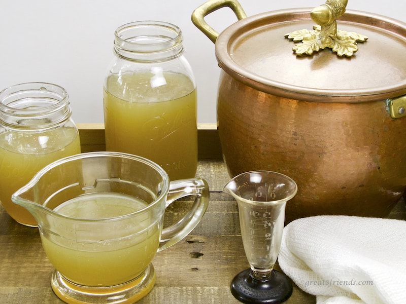 Chicken Stock in jars and measuring cup with copper pot in background