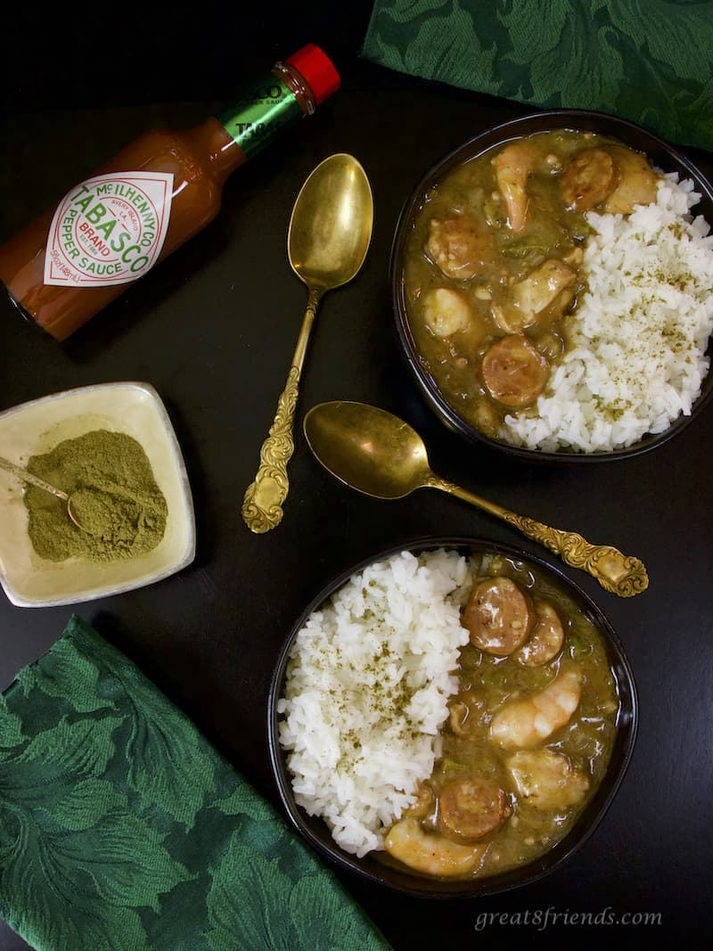 Overhead photo of Two bowls of Sausage Shrimp and Chicken Gumbo with rice, tabasco, and filet powder and gold spoons