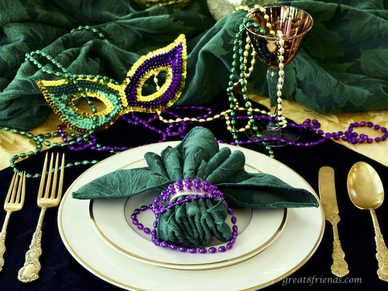Mardi Gras Place Setting with beads, a mask and gold flatware.