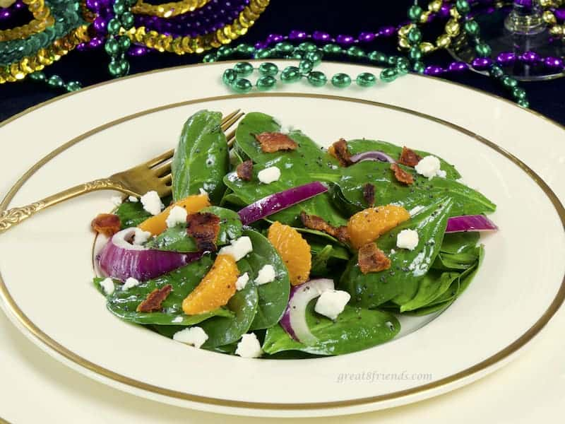 Spinach salad on ivory china with gold rim.