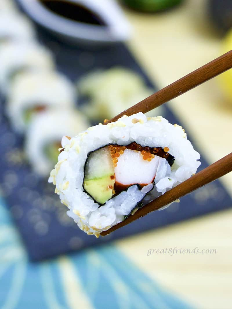 California roll piece held with chopsticks close up