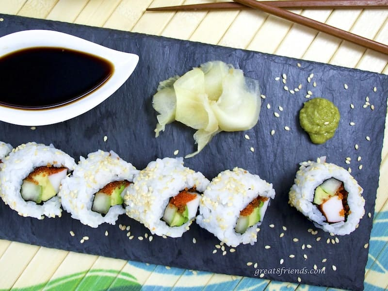 Overhead California Roll on slate with wasabi, ginger, and soy sauce