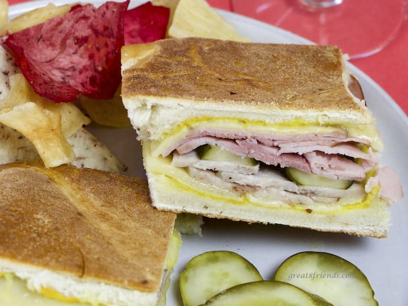 Cubano Sandwich on plate with pickles and Terra chips