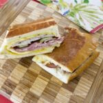 Cubano Sandwich cut in half on cutting board