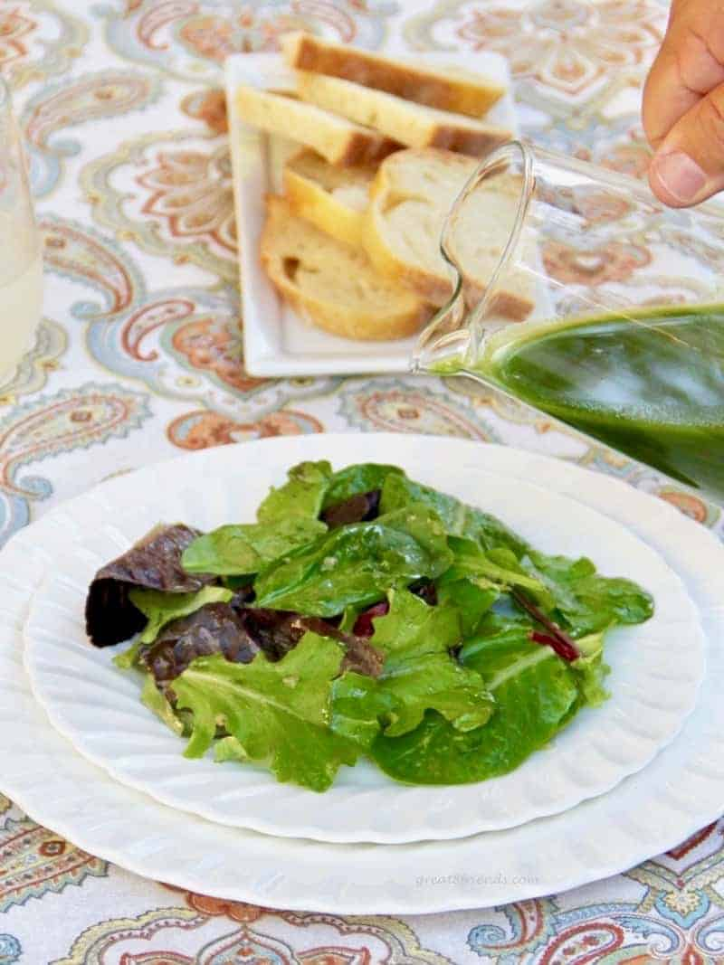 Green salad on a white plate with green arugula lemon salad dressing being poured on with sliced bread in the background.
