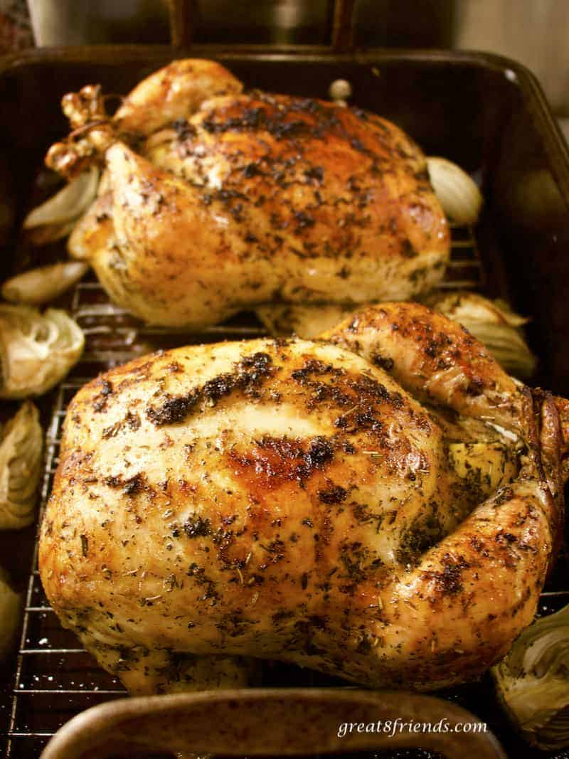 Two whole roast chickens in roasting pan.