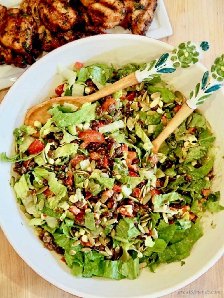 black bean salad in a large bowl with wooden tongs.