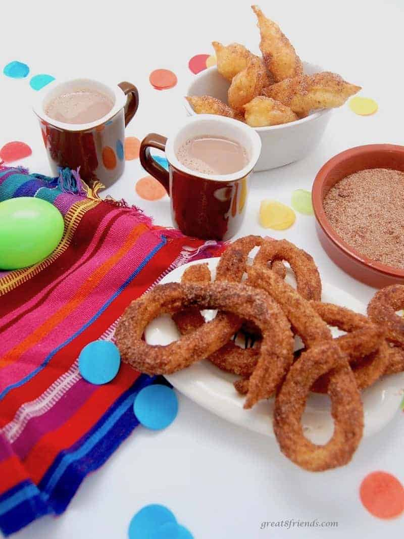 Curly churros with small cups of hot chocolate and a bowl of cinnamon sugar.