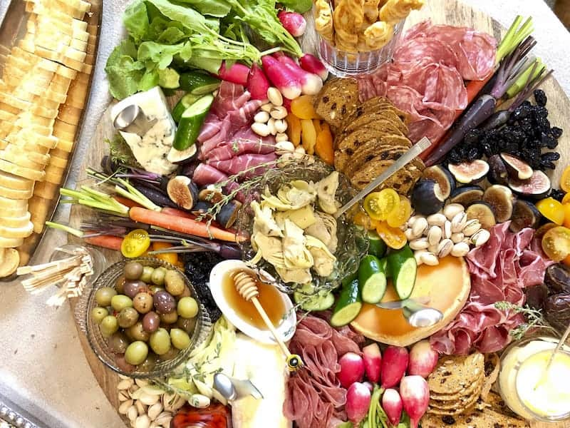 Overhead view of large round grazing board containing meats, cheese, fruits, veggies, crackers, breads, etc.