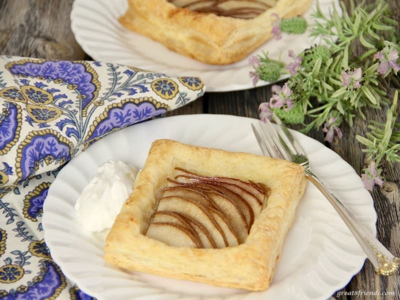 Individual pear tarts served with whipped cream