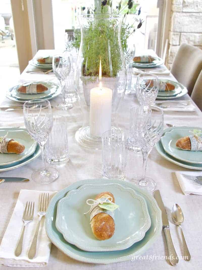 View of table for Provence dinner party, place settings, lit candle in hurricane and centerpiece.