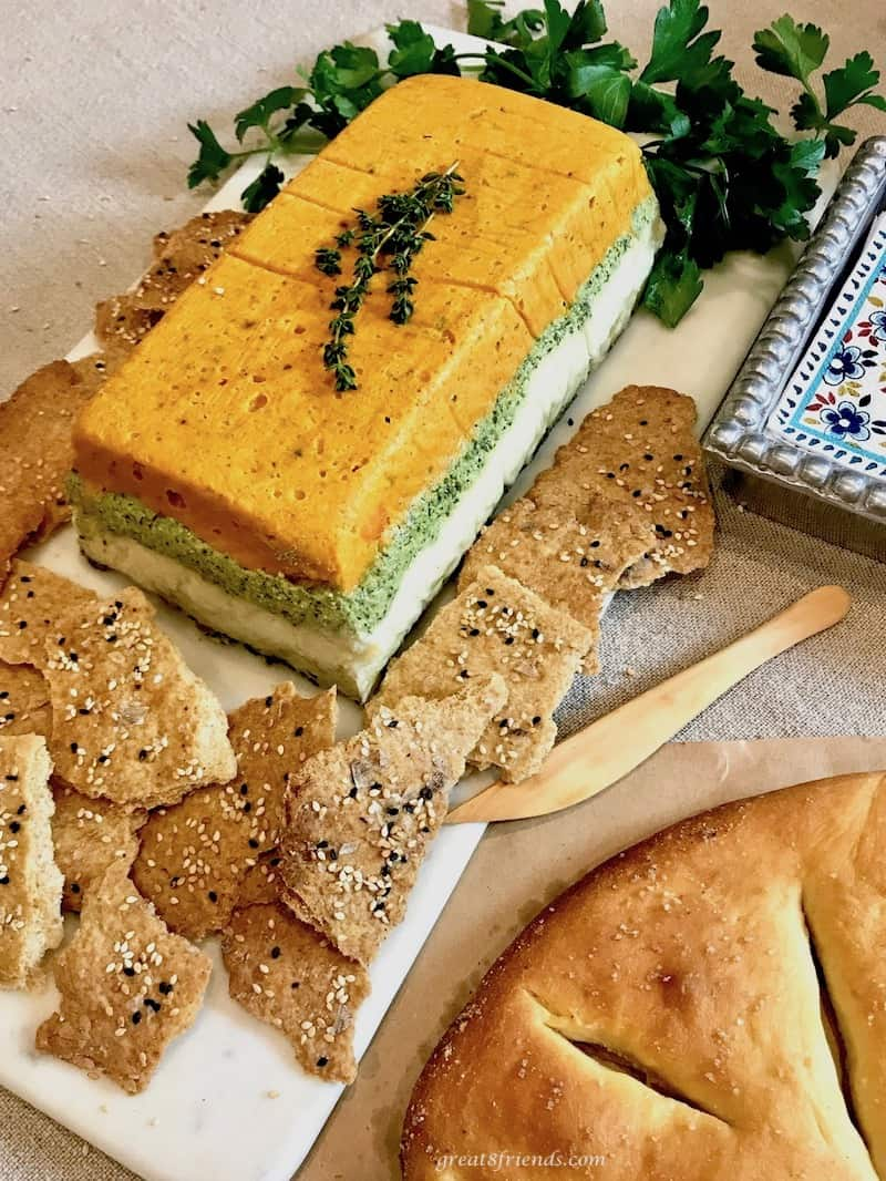 A layered vegetable pâté surrounded by crackers and parsley.