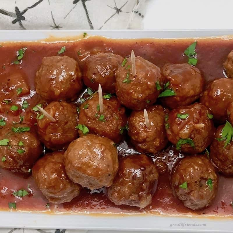 Platter of Hawaiian style meatballs garnished with parsley.