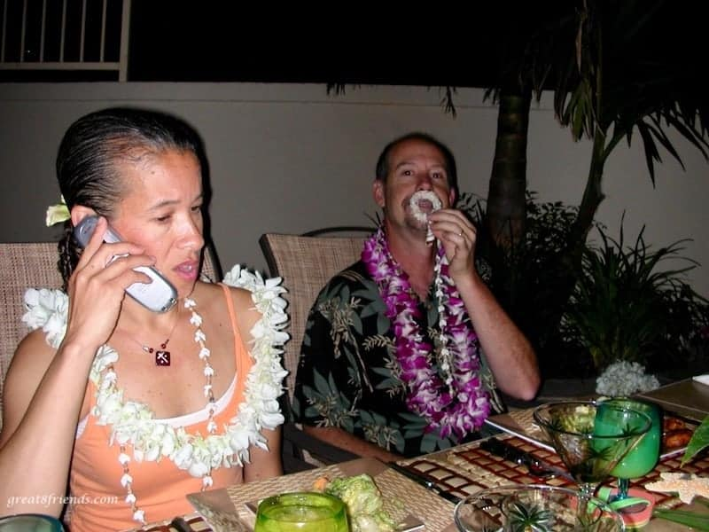 Two people (one on the phone) with Hawaiian leis at a backyard table set for dinner.