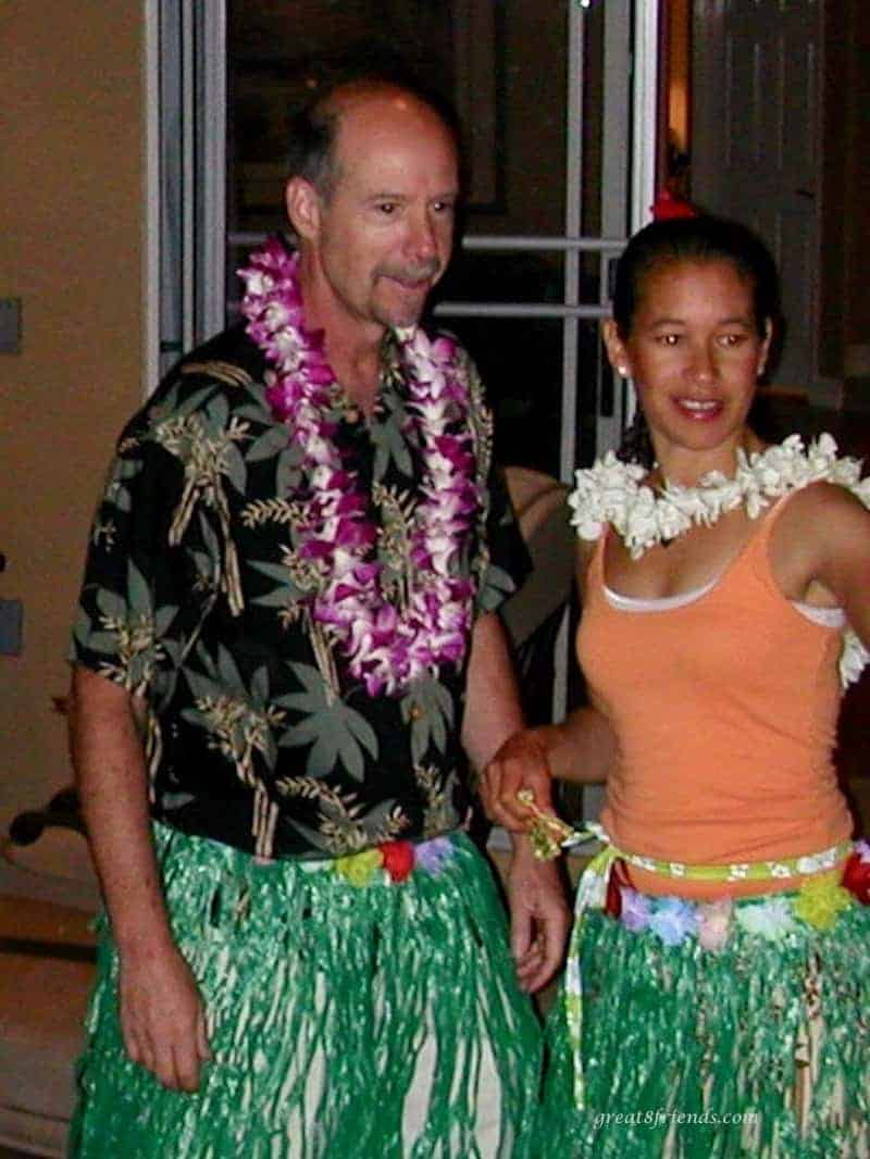 A man and woman with leis on a green grass skirts on.